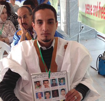 During conference in Algiers, an advocate for self-determination for Western Sahara holds-up a poster with photos of Saharawi activists allegedly jailed by Moroccan authorities.