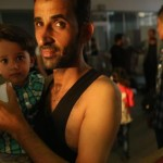 485903492-migrant-from-syria-holds-one-of-his-children-in-a