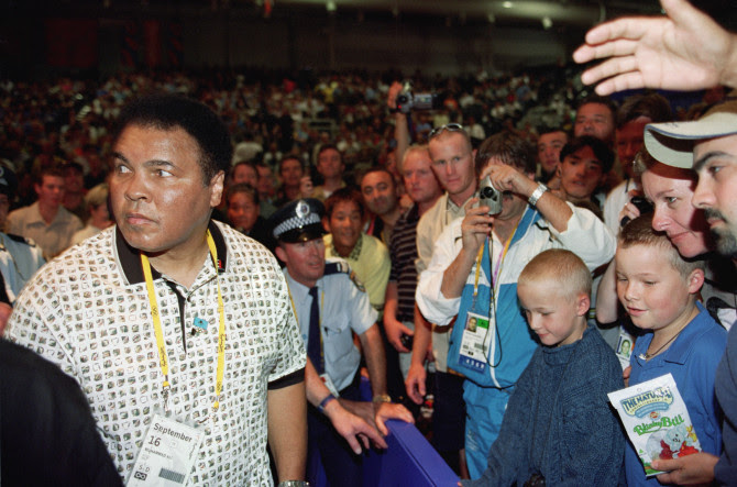 Three-time World Heavyweight Champion Muhammad Ali is greeted by the crowd the men's 54kg boxing bouts at the Sydney Exhibition Centre during the Sydney Olympic Games in Sydney, Australia on September 16, 2000.