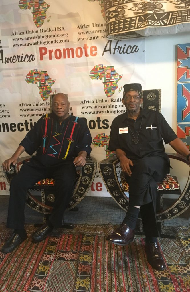 Dr. Molefi Asante and Dr. Ron Daniels enjoy a moment together on African Stools in the Media Center of the African Union Headquarters in Washington, D.C. They were both speakers for the Constituency for Africa's Annual Ron Brown Series. Mel Foote is the President/CEO.