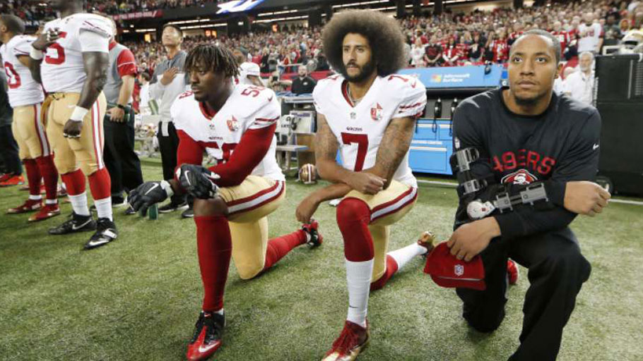 In this Dec. 18, 2016, file photo, San Francisco 49ers quarterback Colin Kaepernick (7) and outside linebacker Eli Harold (58) kneel during the playing of the national anthem before an NFL football game against the Atlanta Falcons in Atlanta. (AP Photo/John Bazemore, File)