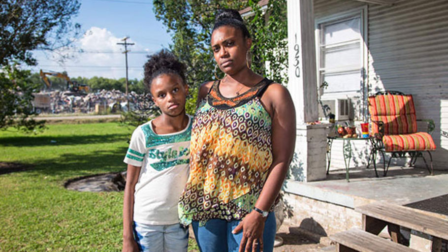 Tami Thomas-Pinkney with her daughter Trinity Handy on their front lawn in Port Arthur, Texas, across from one of the city's temporary dumpsites. (Photo: Julie Dermansky)
