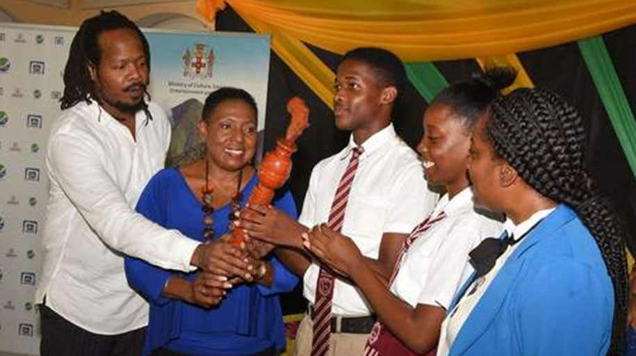 Minister of Culture, Gender, Entertainment, and Sport, Olivia Grange (2nd left), assists in displaying the CARICOM Reparations Youth Relays Baton at the launch of the Jamaican leg of the project yesterday at the Morant Villas in St Thomas. Others (from left) are member of the National Council on Reparations (NCR), Steven Golding; Head Boy at Paul Bogle High School, Daniel Reid; Head Girl at the school, Renae Robinson; and teacher at the institution, Lorraine Williams.
