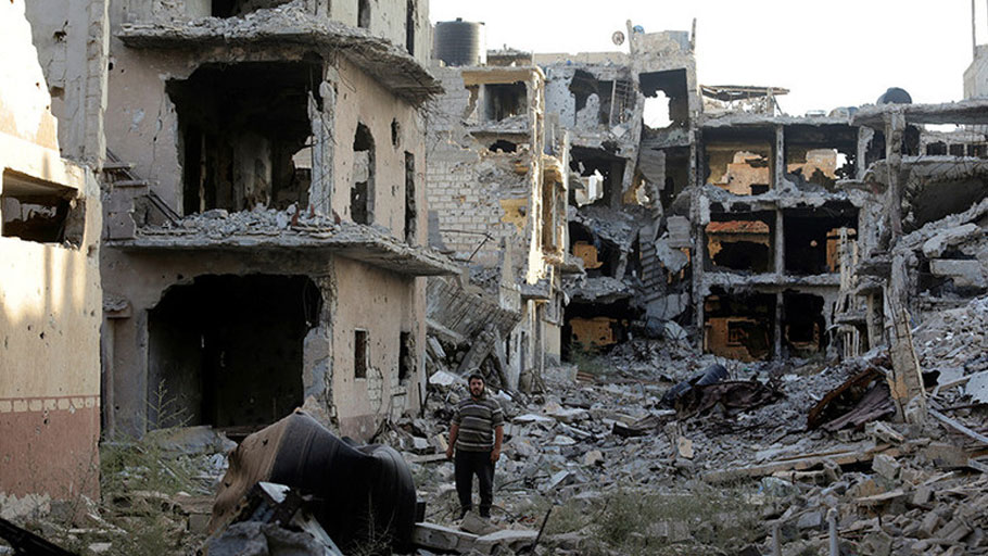 A man stands next to destroyed and damaged buildings in Sabri, a central Benghazi district, Libya