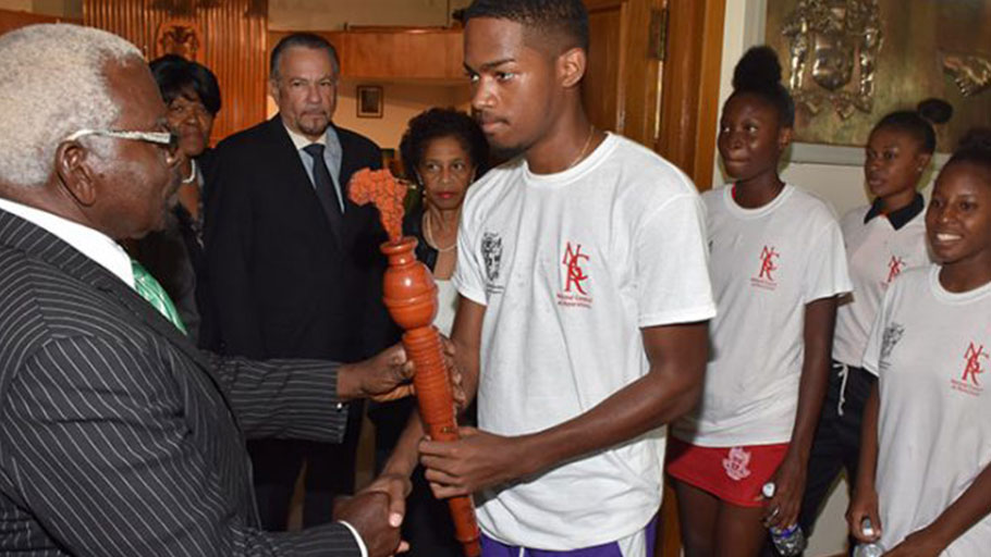 Speaker of the House of Representatives, Hon. Pearnel Charles (left), accepts the relay torch from Karim Murray (fourth right) a participant in the Reparations Youth Baton Relay and Rally. Others observing (from second left) are Deputy Clerk of the Houses of Parliament, Valrie Curtis; President of the Senate, Tom Tavares-Finson; Clerk to the Houses of Parliament, Heather Cooke; and other participants in the relay. The Reparations Youth Baton Relay and Rally is a CARICOM project aimed at building awareness among young people across the region about the issues surrounding the reparations movement and agenda.