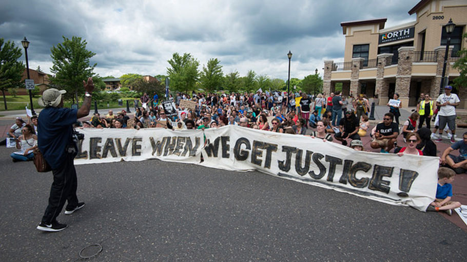 Protesters display a sign during a march against the not-guilty verdict of Jeronimo Yanez, the police officer who shot school teacher Philando Castile, on June 18, 2017, in St. Anthony Village, Minnesota.