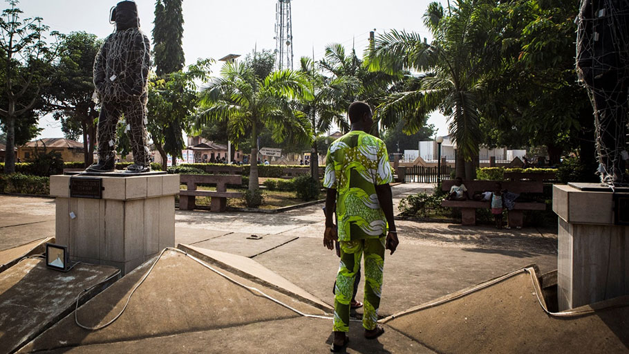 In Ouidah, Benin, a man walks past a statue of Francisco Félix de Souza, a major slave merchant who worked in the 18th and 19th centuries in what is now Benin and is considered the father of the city. The statue is covered with lights.