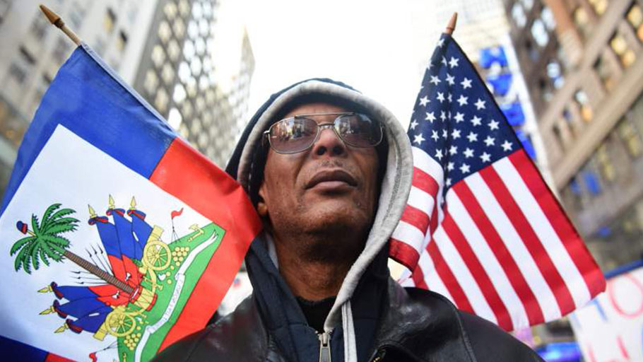 Protestor Pierre Gabriel from Haiti carries flags during a march on Martin Luther King Jr. Day in Times Square, called Rally Against Racism: Stand Up for Haiti and Africa in New York January 15, 2018.