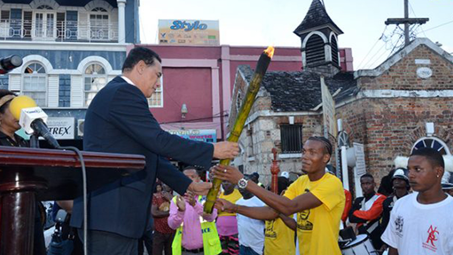Claudia Gardner Mayor of Montego Bay and Chairman of the St. James Municipal Corporation, Councillor Homer Davis (left), accepts the Flames of Freedom Emancipation Torch from Javon Mendis of Maroon Town, during the Western Jamaica Leg of the CARICOM Reparations Youth Baton Relay and Rally, which took place in Sam Sharpe Square on December 27.