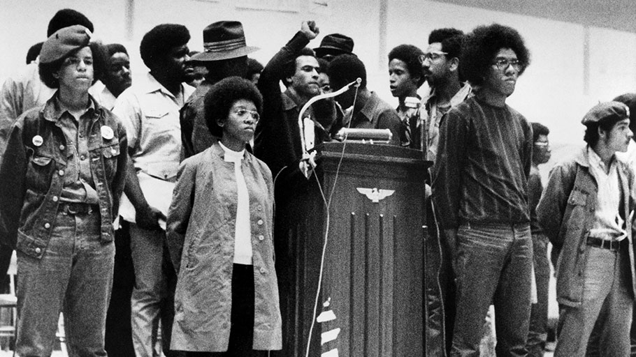 Huey P. Newton, national defense minister of the Black Panther Party, raises his clenched fist behind the podium as he speaks at a convention sponsored by the Black Panthers at Temple University's McGonigle Hall in Philadelphia, Pa., Saturday, Sept. 5, 1970. He is surrounded by security guards of the movement. The audience gathered is estimated at 6,000 with another thousand outside the crowded hall.