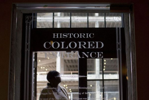 Woman stands in the doorway of then new Historic Colored Entrance at the Lyric Theatre, in Birmingham, Ala