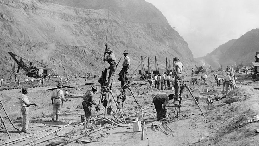 Panama Canal construction in 1913 showing workers drilling holes for dynamite in bedrock, as they cut through the mountains of the Isthmus. Steam shovels in the background move the rubble to railroad cars.