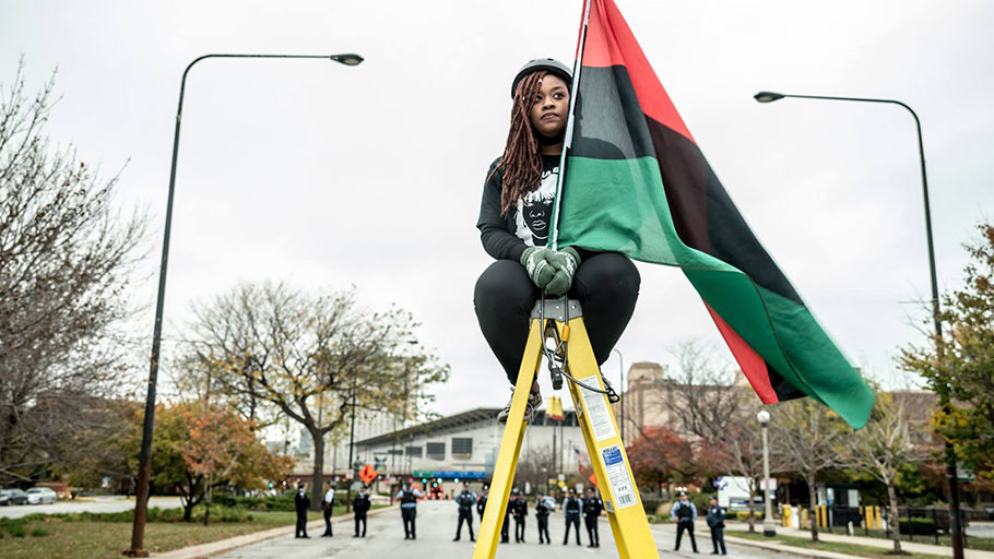 An activist holds a Pan-African flag during a protest disrupting the Association of Chiefs of Police Conference on October 25, 2015, in Chicago, Illinois.
