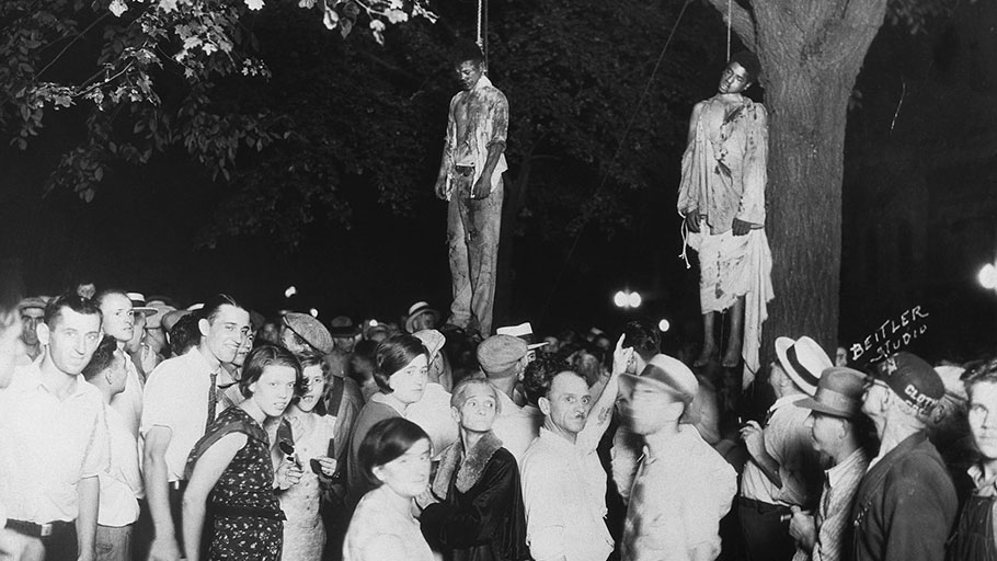 A crowd gathers after the lynching of two young African American men who were taken from the Grant county jail, in Marion, Indiana, and lynched in the public square. Photograph: Lawrence Beitler/Bettmann Archive
