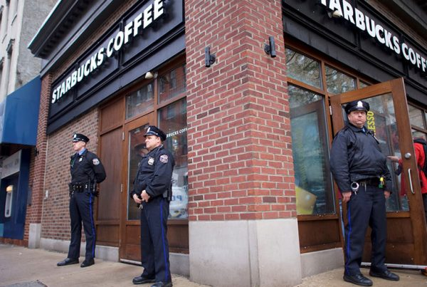 Police officers monitor activity outside as protesters demonstrate inside a Philadelphia Starbucks, where two men were arrested.