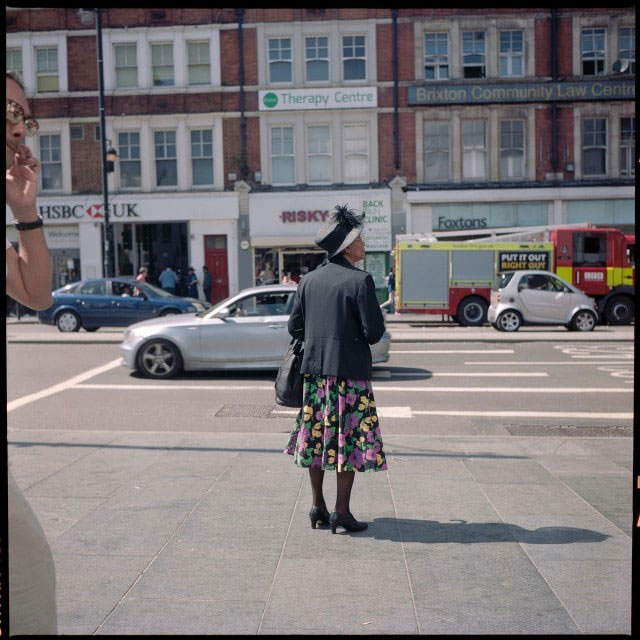 A woman waits for a bus in Brixton.