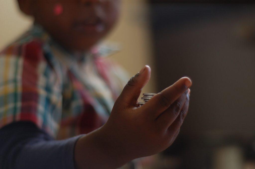 Black child holding coins - Serede Jami / Eyeem / Getty Images