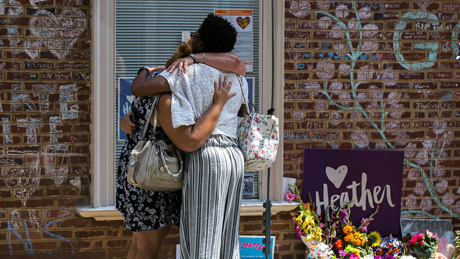 Mourners embrace in front of chalk messages that line the walls outside the buildings where Heather Heyer was killed by a speeding vehicle as she was protesting the Unite The Right rally in Charlottesville, Virginia. Photograph: Logan Cyrus/AFP/Getty Images