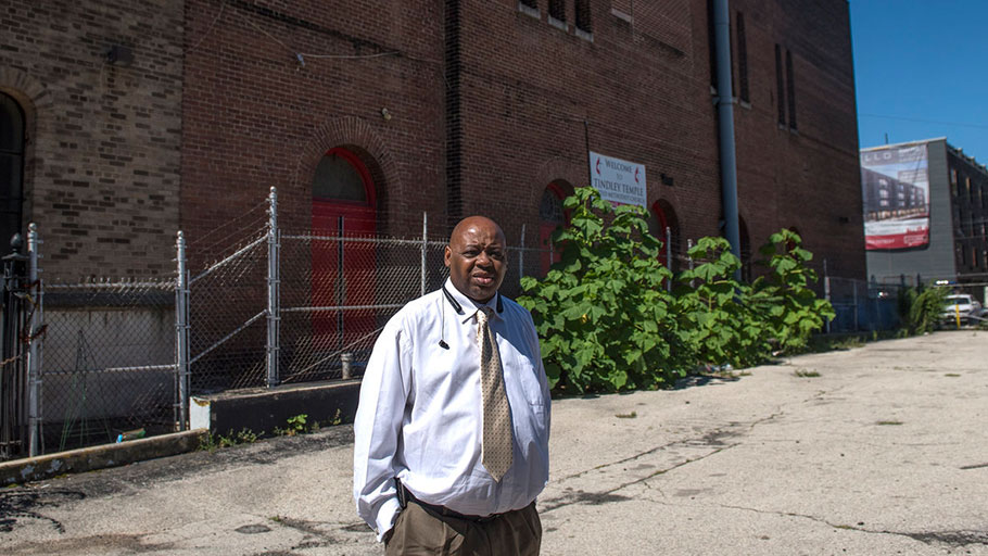 Rev. Robert Johnson stands on the Broad Street next to his church where a New York developer is planning to build $2 million townhouses.