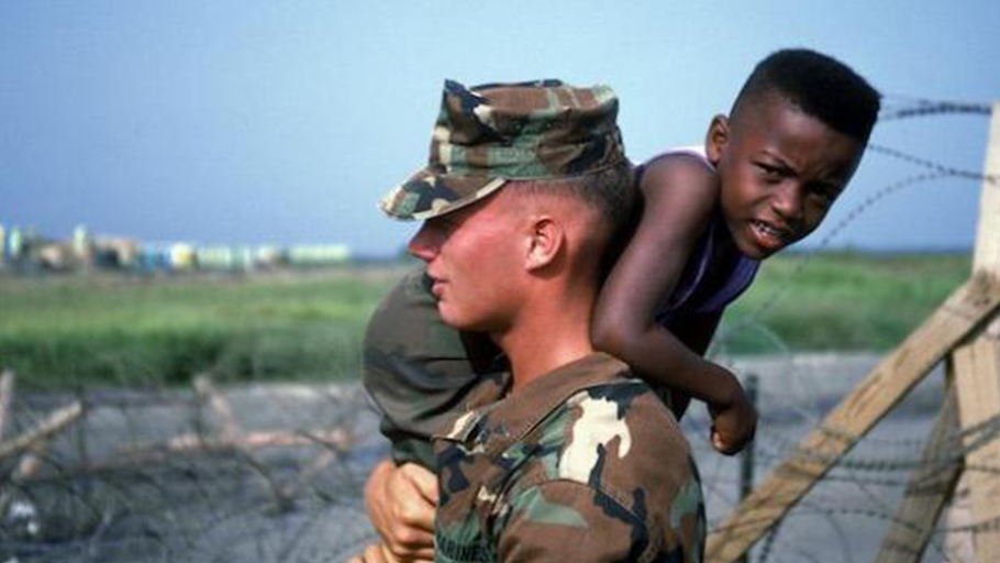 A marine carries a Haitian refugee child at Camp McCalla in Guantánamo Bay in 1992