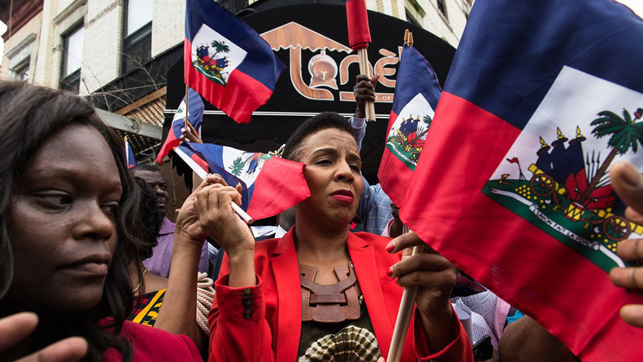 Laurie Cumbo, center, the City Council majority leader, and Assemblywoman Rodneyse Bichotte, left, passed out Haitian flags.