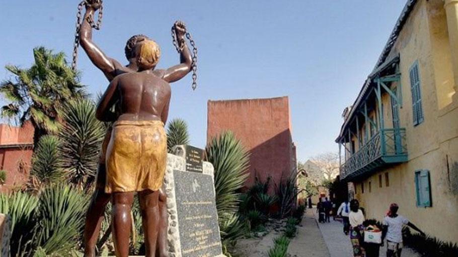 Senegalese women walk past a monument to slavery near the Slave house on Goree island 3km off Dakar, Senegal