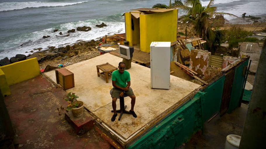 In this photo from October 2017, Roberto Figueroa Caballero sits in the ruins of his home after Hurricane Maria.