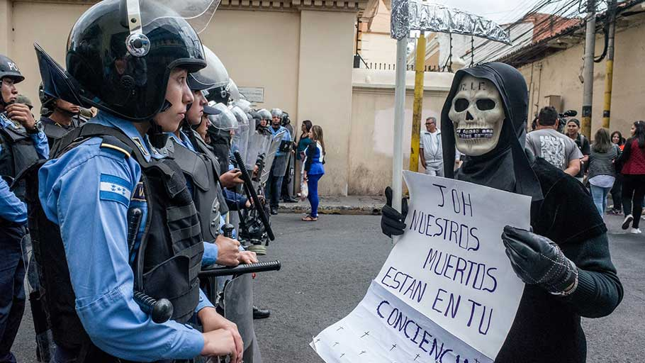 "A woman dressed as death stands in front of Honduran security forces during protests in the capital, Tegucigalpa, with a sign that reads, ""JOH [Juan Orlando Hernández] our deaths are on your conscience."