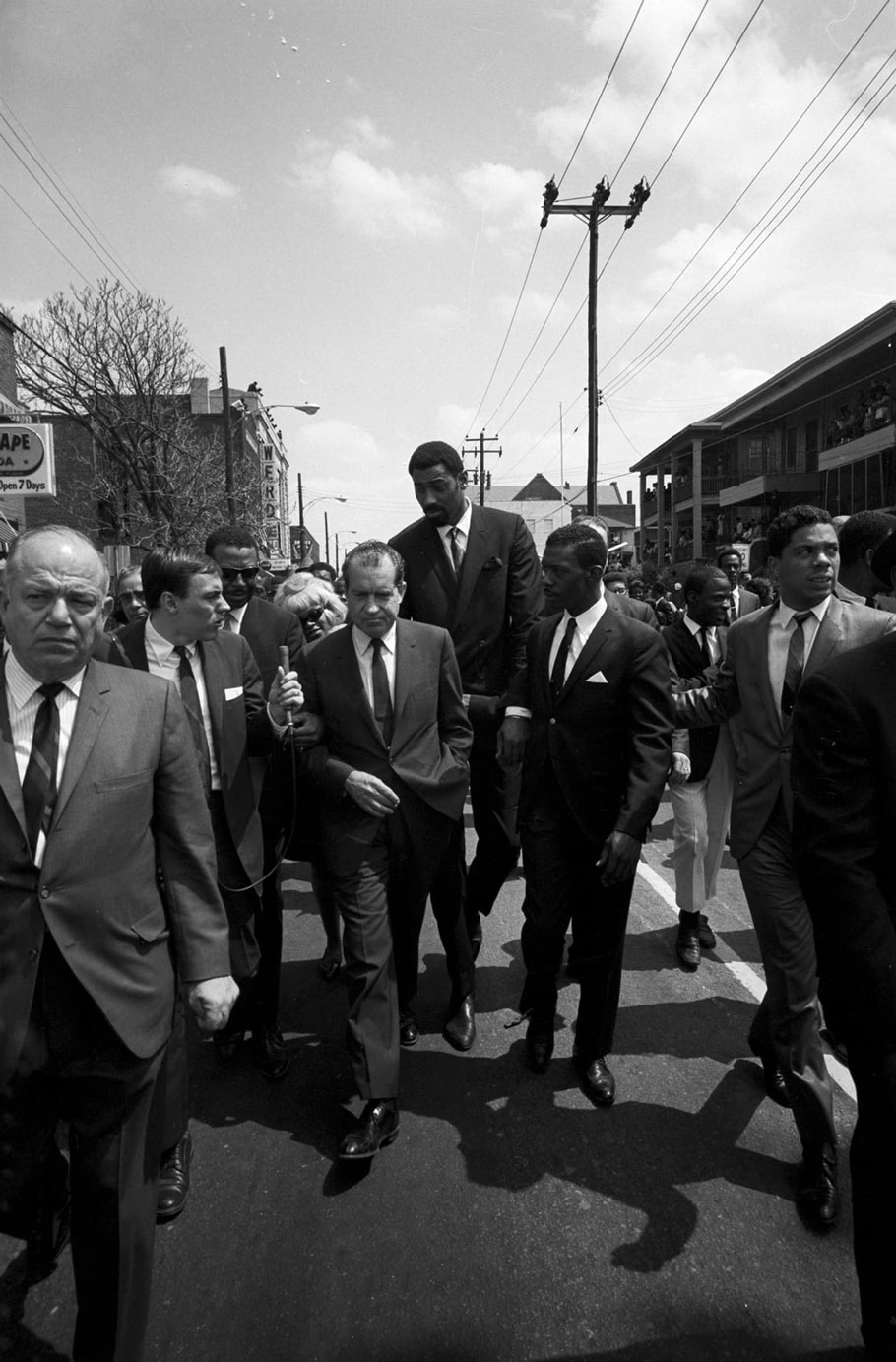 At the funeral of Dr. Martin Luther King Jr., Richard Nixon, surrounded by bodyguards, follows the funeral procession.