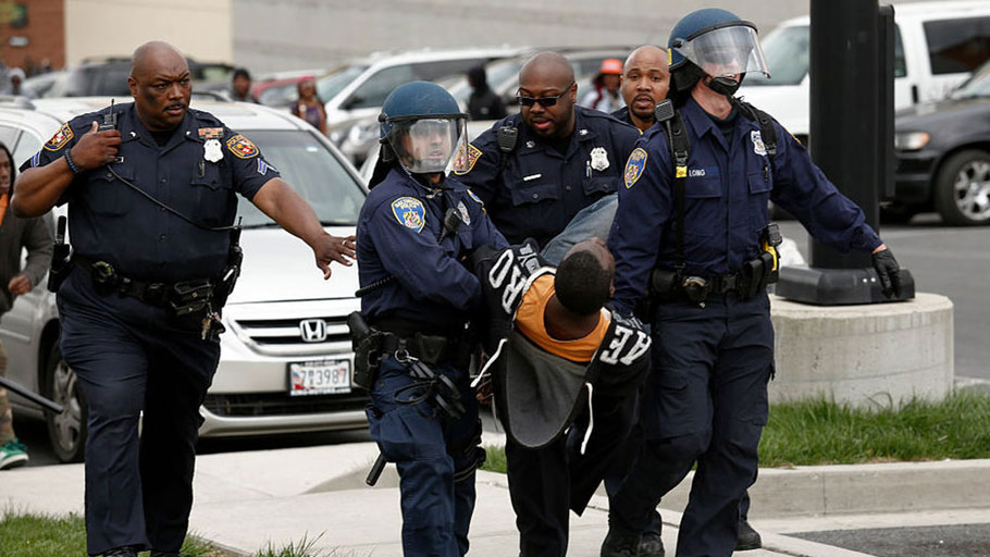 BALTIMORE, MD - APRIL 27: Baltimore Police officers arrest a man near Mowdamin Mall, April 27, 2015 in Baltimore, Maryland. The funeral service for Freddie Gray, who died last week while in Baltimore Police custody, was held on Monday morning.