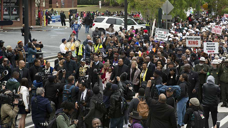Hundreds participate in the commemorative march retracing part of Martin Luther King Jr.'s funeral procession that happened 50 years prior. Fifty years earlier, thousands of people walked behind Martin Luther King Jr.'s casket as it was drawn by mules from Ebenezer Baptist Church to Morehouse. Image by Evey Wilson