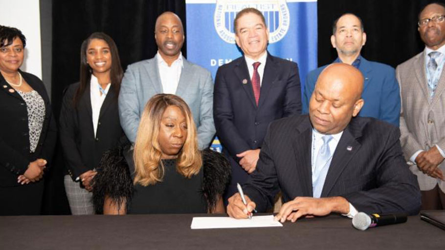 Lois Johnson, ceo and founder of of Salt Lake City, Utah-based United Security Financial (USF) and NAREB president Jeffrey Hicks(Front) sign the landmark $50 million agreement making down payment assistance funds available to expand homeownership opportunities for low and moderate-income Black American home purchasers. Witnessing the signing at NAREB's Mid-Winter Conference in Miami, FL are: (2nd Row, L-R) Lydia Pope, NAREB 1st VP; Sumari Barnes, personal assistant to LJ Jennings; Tim Johnson, VP, Secondary Markets, USF; Michael Grant, regional president, USF; LJ Jennings, president, NAREB Sales Division affiliate, and Robert Hughes, chair, NAREB board of directors.