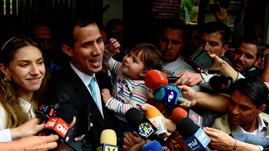 Opposition leader and self-proclaimed 'acting president' Juan Guaido (2-L) talks to the press as he holds his daughter Miranda (3-L), next to his wife Fabiana Rosales (L), outside his home in Santa Fe, Caracas on January 31, 2019. - Venezuela's self-proclaimed acting president Juan Guaido on Thursday accused socialist leader Nicolas Maduro's security forces of trying to intimidate his family. Guaido, the opposition leader challenging Maduro's rule, said the security service FAES had gone to his house asking for his wife, Fabiana.