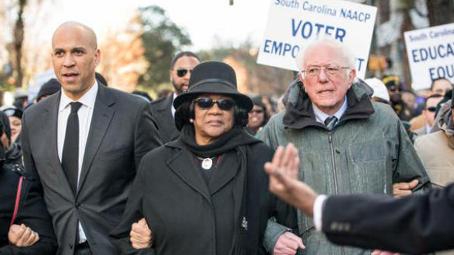 Sens. Cory Booker and Bernie Sanders, seen at a South Carolina NAACP march in January, are two of the 2020 Democratic presidential candidates pressed on the issue of reparations this week.,