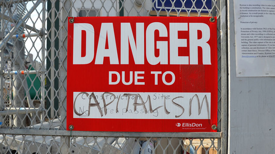 "A sign posted on a construction site says, ""Danger Due to Capitalism."""