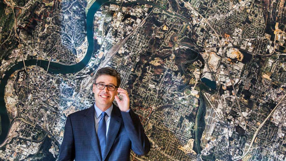 Chattanooga, Tennessee, Mayor Andy Berke stands in front of an aerial image of the city in November 2014. Berke has been a major promoter of the city's high-speed municipal fiber optic network.