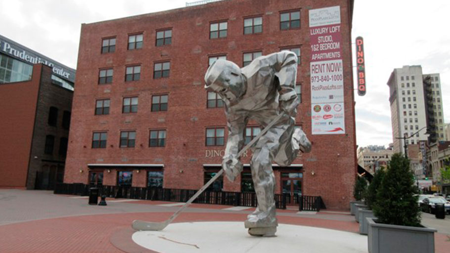 """The Iron Man"" sculpture of a hockey player next to the Prudential Center in Newark, where the New Jersey Devils hockey team plays. In the background, signs can be seen for Dinosaur Bar-B-Cue BBQ and Rock Plaza Lofts luxury apartments."