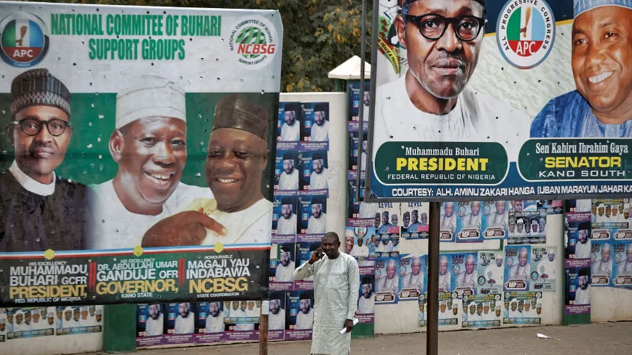 A man takes a call as he stands between two billboards showing Nigeria's President Muhammadu Buhari and other party officials, in Kano, northern Nigeria, February 26, 2019