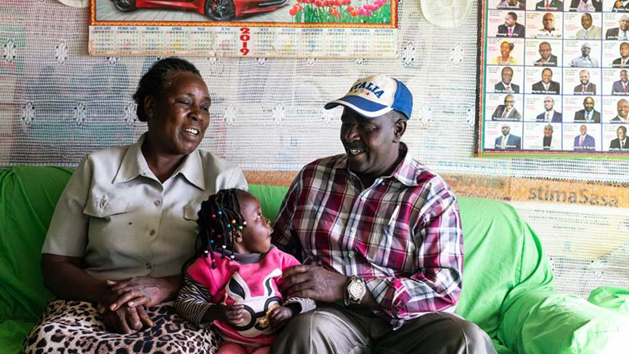 Charles Gichuhi Ngari sits with his wife, Esther Wairimu Gichuhi, and granddaughter Rose Wamboi Njoroge at their home in Embaringo, Kenya