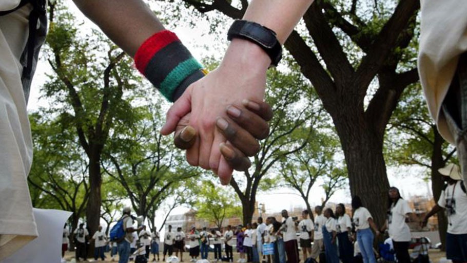 Cardrian Massey, left, and Kate Chandler hold hands in a circle with others from Atlanta, Ga., before joining demonstrators for reparations for slavery on the National Mall in Washington.