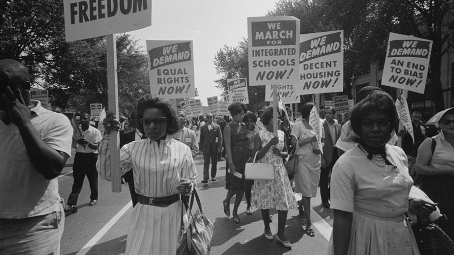 Civil rights advocates carry placards during the March on Washington for Jobs and Freedom on August 28, 1963, in Washington