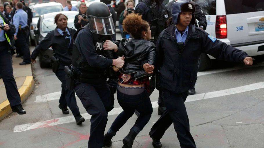 A demonstrator protesting the murder of Michael Brown is arrested by cops in riot gear on November 30, 2014, in St. Louis, Missouri.