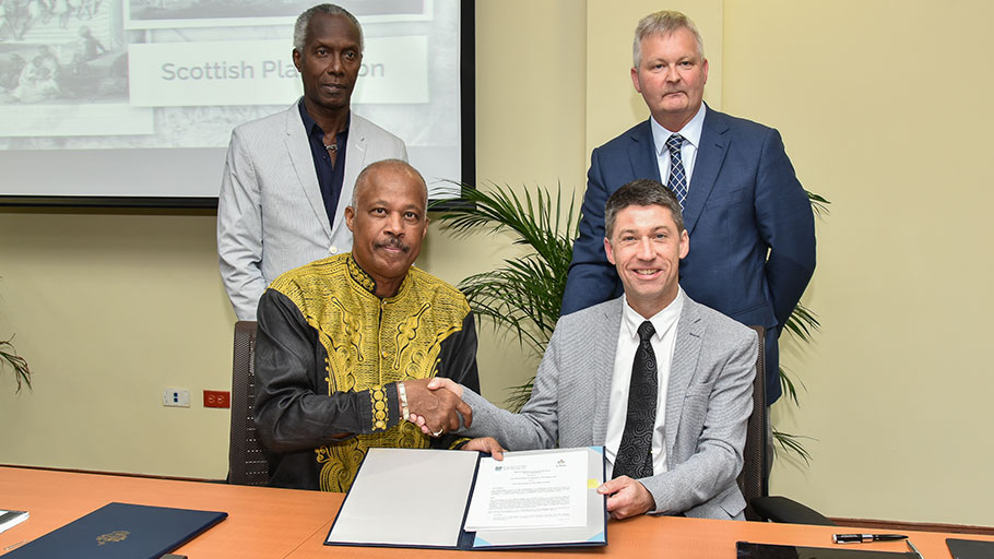 Professor Sir Hilary Beckles (seated left), Vice-Chancellor of The University of the West Indies (The UWI) and Dr. David Duncan, Chief Operating Officer & University Secretary, University of Glasgow, shake hands following the signing of the Memorandum of Understanding at The UWI Regional Headquarters, Kingston, Jamaica on July 31, 2019, to partner in a reparations strategy including the establishment of the Glasgow-Caribbean Centre for Development Research. Witnessing the event are C. William Iton (left), University Registrar, The UWI and Peter Aitchison, Director of Communications & Public Affairs, University of Glasgow.