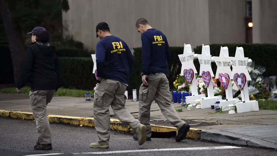 FBI agents walk past a memorial outside the Tree of Life synagogue in Pittsburgh