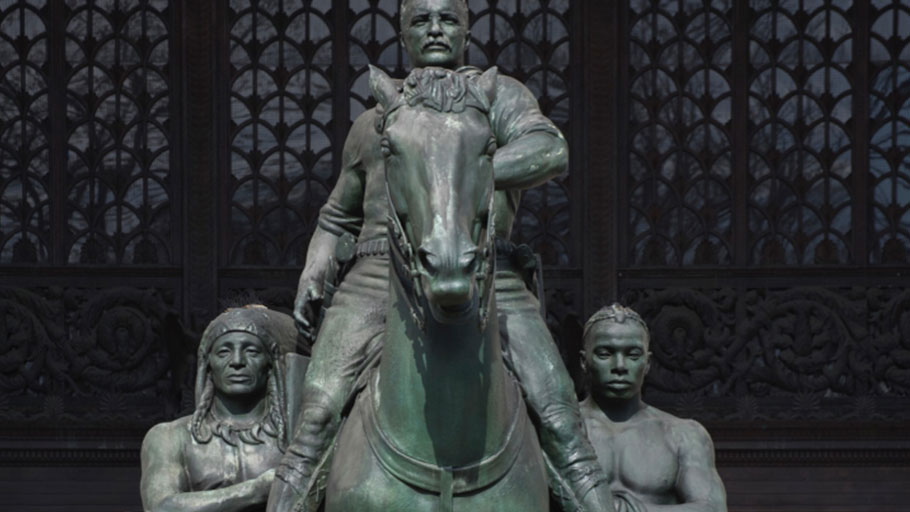 The statue depicts Roosevelt on horseback, with a Native American man and an African man