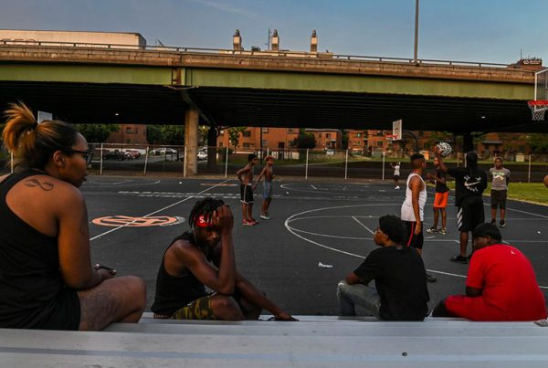 Kids play basketball at Wilson Park near where Interstate 81 slices through a public housing complex in Syracuse, N.Y.