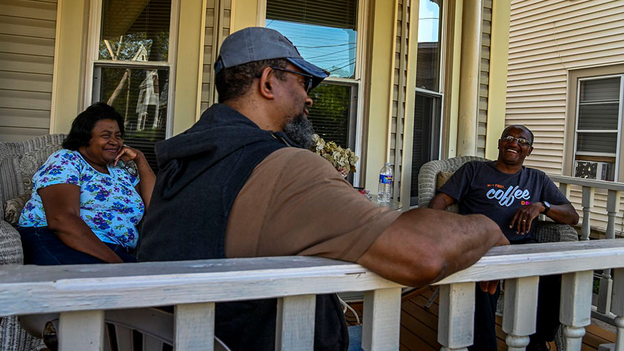 Bebe Baines, left, and husband Lloyd Baines sit with neighbor David Abdul Sabur, center, on their front porch that is only a stone's throw from I-81.