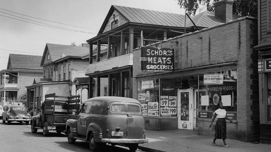 A woman walks past Schor's Market on Harrison Street in Syracuse's 15th Ward in 1965.