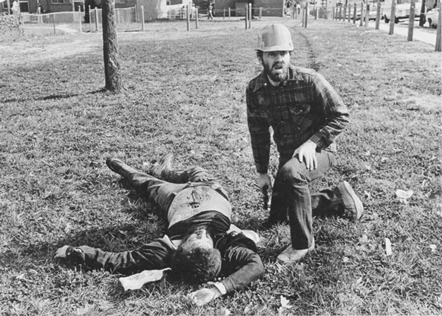 A WVO member kneels beside a victim of the shooting.