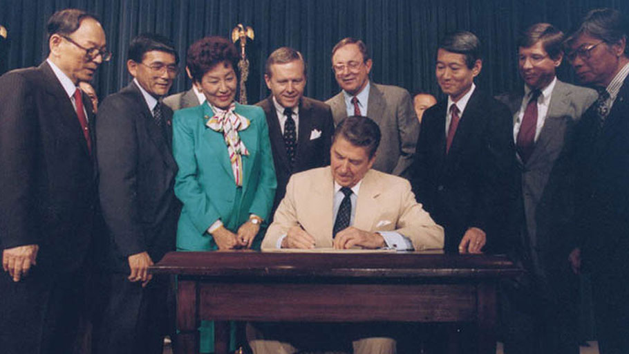 President Reagan signs the Civil Liberties Act of 1988, which granted reparations to Japanese Americans
